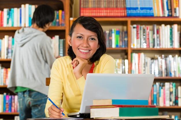 Jeune fille dans la bibliothèque avec un ordinateur portable