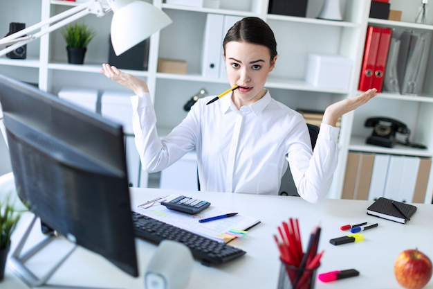 Une jeune fille dans le bureau est assise à une table, tenant un stylo dans la bouche et écartant les mains.