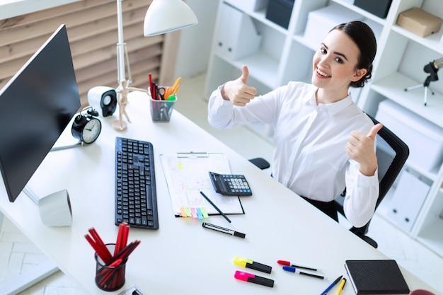 Une jeune fille dans le bureau est assise à une table, travaille avec des documents et montre un signe de classe.