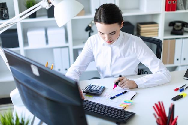 Une jeune fille dans le bureau est assise à une table, travaille avec un ordinateur et écrit un marqueur rose sur le document.