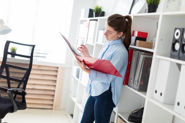 Une jeune fille dans le bureau se tient près du refuge et fait défiler le dossier avec les documents.