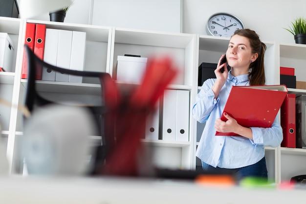 Une jeune fille dans le bureau se tient près du refuge, parle au téléphone et fait défiler le dossier contenant les documents.