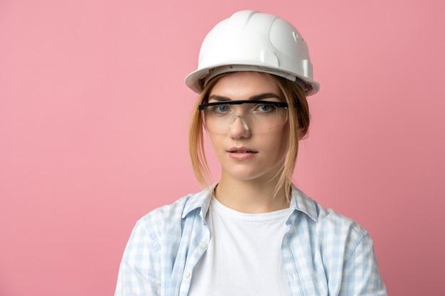 Jeune fille dans un casque de construction sur fond d'un mur rose