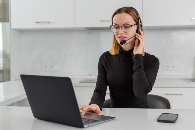 Une jeune fille dans un casque avec un microphone travaille dans un centre d'appels assis devant un ordinateur portable à la maison dans la cuisine. photo de haute qualité