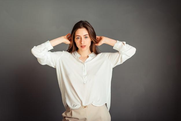 Jeune fille dans une chemise blanche sur un mur gris. la jeune fille a l'air droite, les mains près de sa tête penchée aux coudes. sans retouche. sans maquillage.