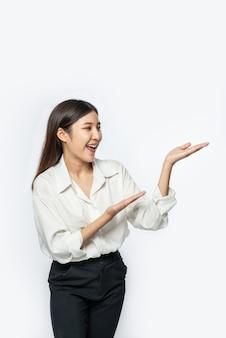 La jeune fille dans une chemise blanche et le signe de la main ouverte sur le côté