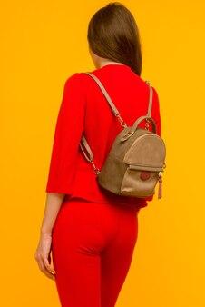 Jeune fille dans un costume rouge avec un petit sac à dos sur fond jaune