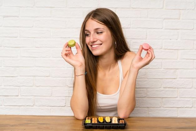 Jeune fille dans une cuisine avec des macarons