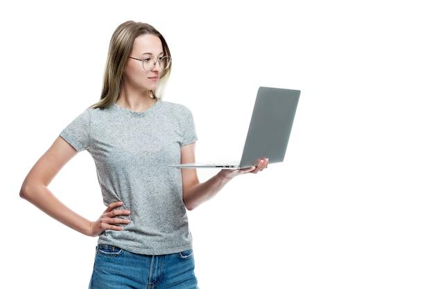 Une jeune fille dans un débardeur gris et un jean avec un ordinateur portable dans les mains. blog et communication. . espace pour le texte.