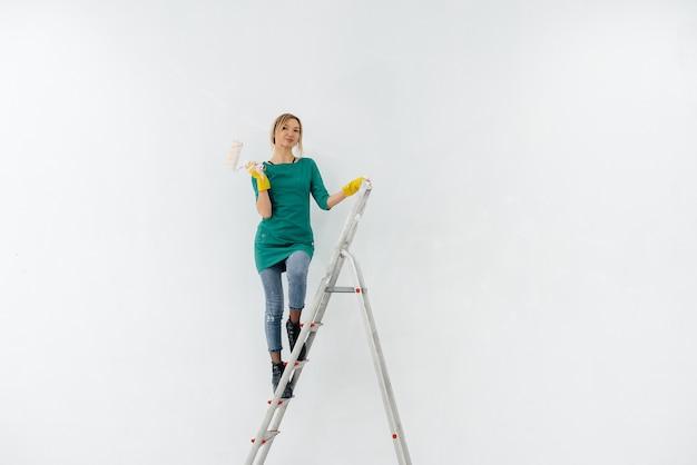 Une jeune fille dans les escaliers peint un mur blanc avec un rouleau. réparation de l'intérieur.