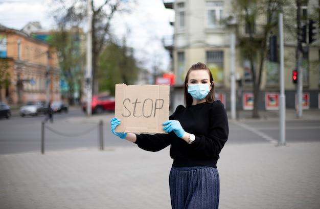 Jeune fille dans des gants et un masque tient une bannière et montre une protestation