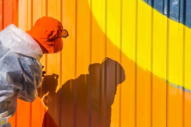Une jeune fille dans un manteau blanc avec des taches de peinture graffiti de clôture en fer nervuré