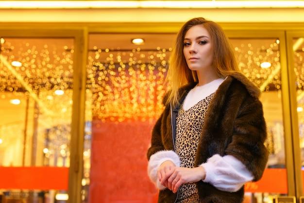 Jeune fille dans un manteau de fourrure posant pour l'ambiance festive de la caméra