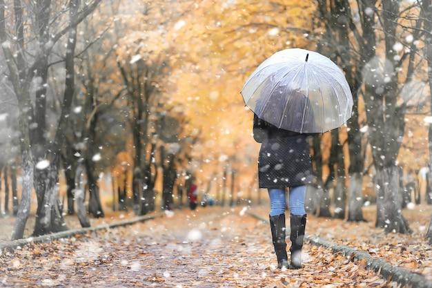 Une jeune fille dans le parc lors d'une promenade dans les premières chutes de neige