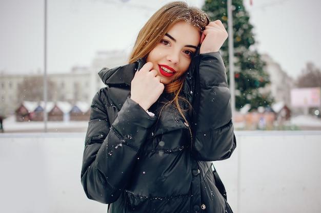 Jeune fille dans un pull blanc, debout dans un parc d'hiver