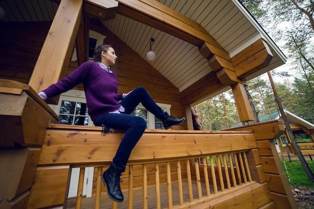 Jeune fille dans un pull violet et un jean noir sur le porche d'une maison en bois
