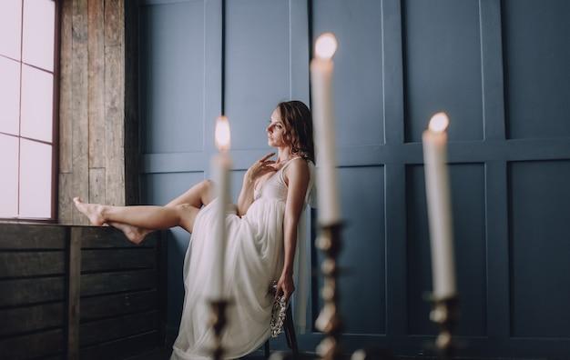 Jeune fille dans une robe blanche à l'intérieur dans une pièce se trouve près d'une fenêtre