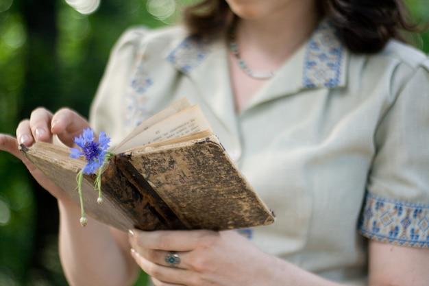Une jeune fille dans une robe vintage tenant un vieux livre