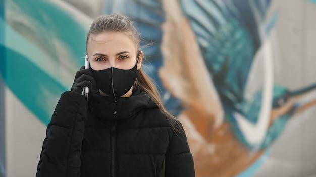 Jeune fille dans la rue de la ville portant un masque facial médical stérile noir. femme utilisant le téléphone pour rechercher des nouvelles sur ncov 2019. quarantaine covid-19 pandémie de coronavirus pandémique et concept de soins de santé