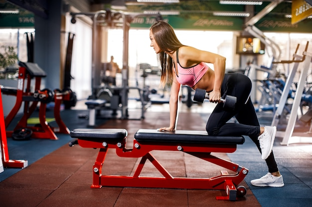 La jeune fille dans la salle de gym s'accroupit avec une barre.