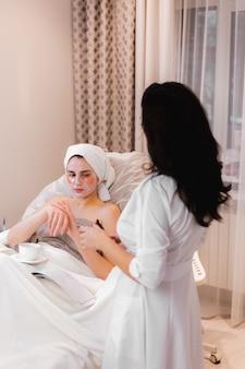 Une jeune fille dans un salon de beauté dans un bureau de cosmétologie se trouve sur le lit se détend avec un masque sur son visage