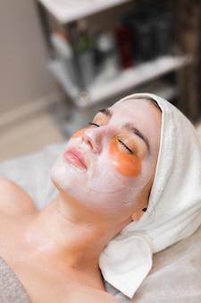 Une jeune fille dans un salon de beauté dans une salle de cosmétologie se trouve sur un lit se détend avec un masque sur son visage et des taches sous ses yeux