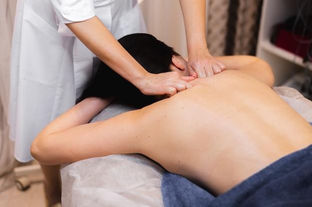 La jeune fille dans le salon spa reçoit un massage du dos et de la nuque, se trouve dans la table de cosmétologie, détendue et apprécie le processus