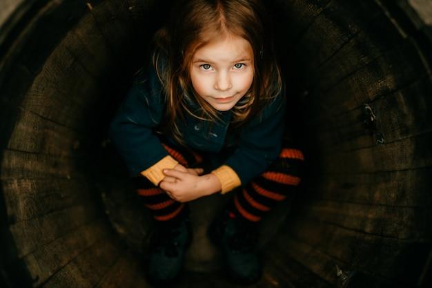 Jeune fille dans un tonneau en bois