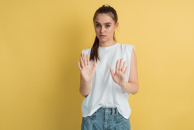 Jeune fille dans un tshirt blanc montrant un geste d'arrêt avec des paumes à la caméra sur un fond jaune.