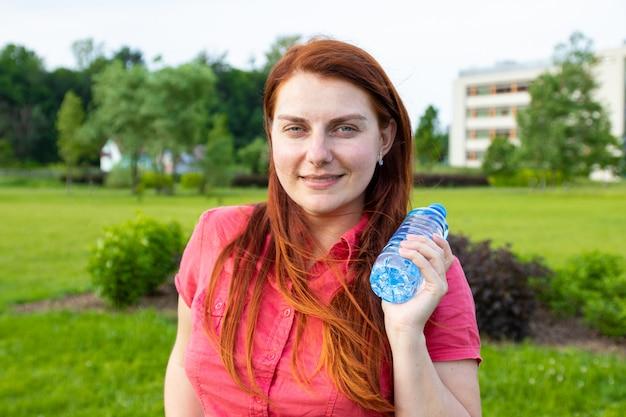 Jeune fille dans des vêtements d'été brillants est titulaire d'une bouteille d'eau en plastique