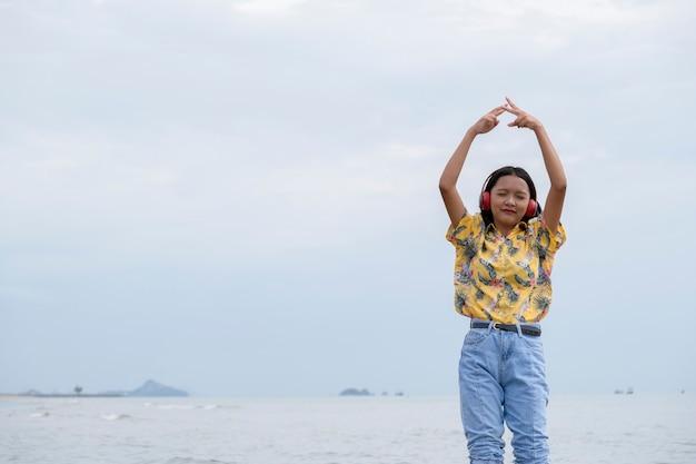 Jeune fille dansant et écoutant de la musique sur une belle plage.