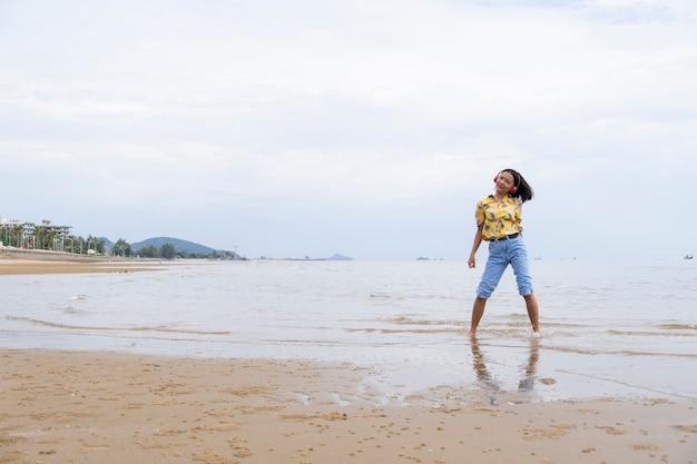 Jeune fille dansant et écoutant de la musique à la plage.