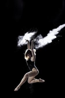 Jeune fille dansant avec une farine sur le fond noir sur le sceene