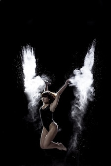 Jeune fille dansant avec une farine sur fond noir