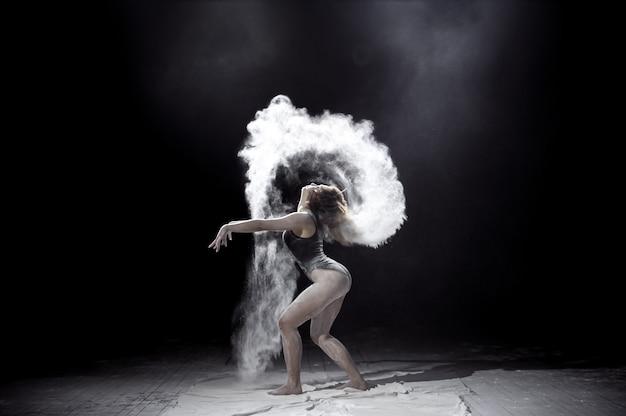 Jeune fille dansant avec une farine sur fond noir.
