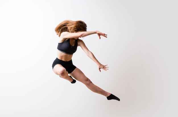 Jeune fille danse sur mur blanc isolé