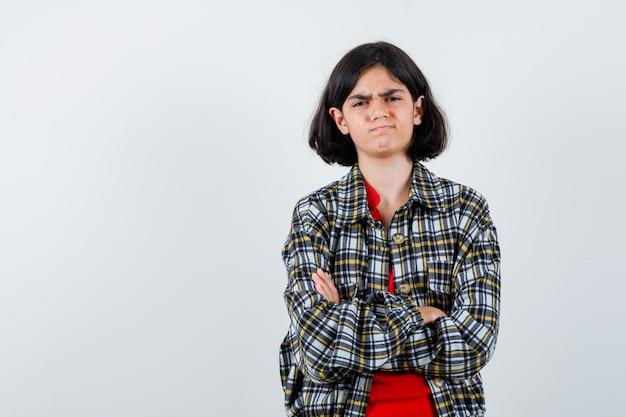 Jeune fille debout les bras croisés dans une chemise à carreaux et un t-shirt rouge et l'air sérieux, vue de face.