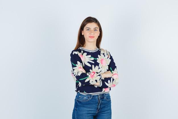 Jeune fille debout les bras croisés dans un pull à fleurs, un jean et l'air confiant, vue de face.