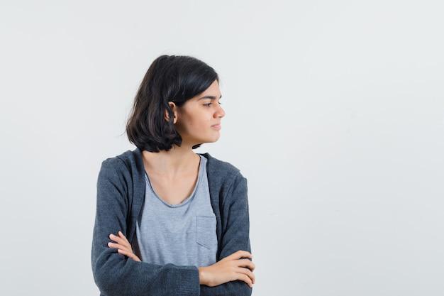 Jeune fille debout les bras croisés, regardant ailleurs en t-shirt gris clair et sweat à capuche zippé gris foncé et à mignon,