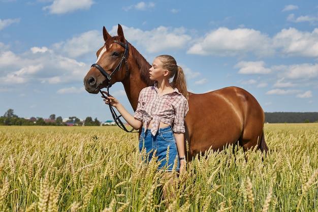 Jeune fille debout à côté du cheval dans le champ