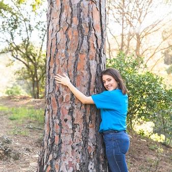 Jeune fille, debout, dans, bois, et, étreindre, arbre
