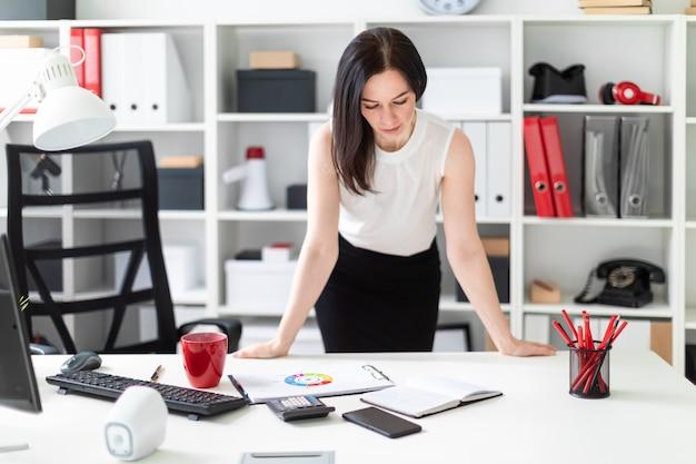 Une jeune fille debout dans le bureau près du bureau de l'ordinateur.