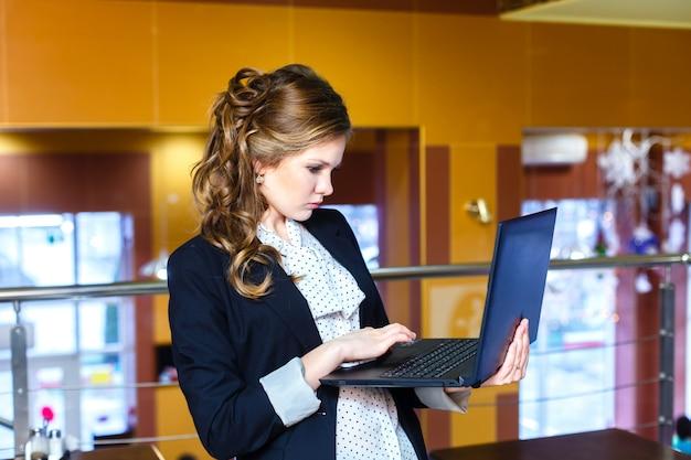 Jeune fille debout dans un café et travaillant sur un ordinateur portable