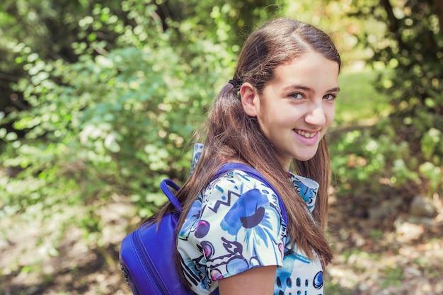 Jeune fille debout dans le parc en souriant