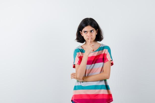 Jeune fille debout dans une pose de réflexion, mettant l'index sur la bouche tout en détournant les yeux dans un t-shirt rayé coloré et l'air pensif, vue de face.