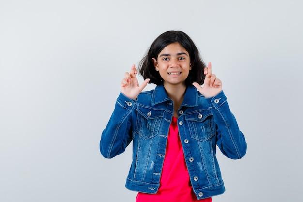 Jeune fille debout les doigts croisés en t-shirt rouge et veste en jean et l'air heureux. vue de face.