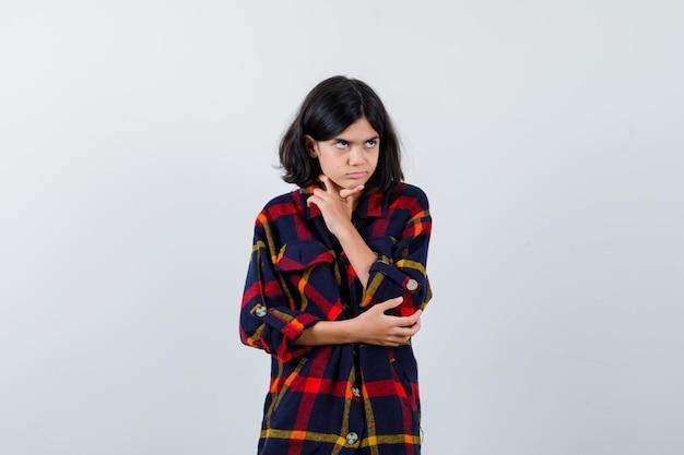 Jeune fille debout en pensant pose en chemise à carreaux et à la pensive, vue de face.