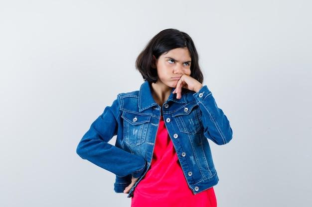 Jeune fille debout en pensant pose en t-shirt rouge et veste en jean et regardant pensive, vue de face.