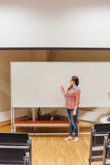 Jeune fille debout près du tableau blanc