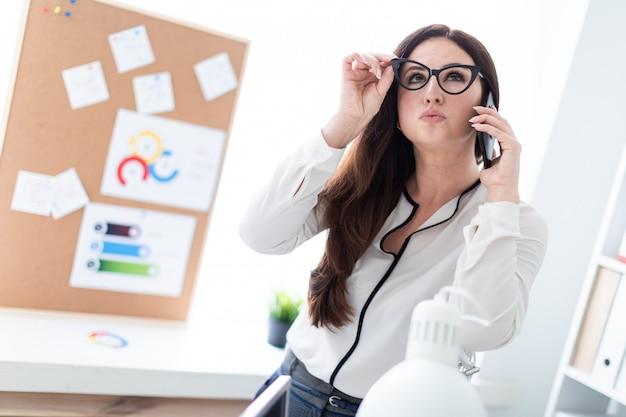 Une jeune fille debout près de la table et parlant au téléphone.